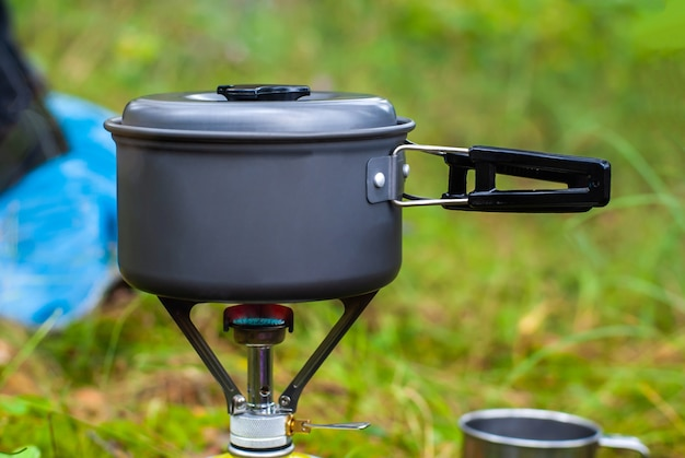 Cooking in the mountain hike on a gas burner in a bowler hat