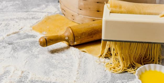 麺を調理します。めん棒と卵のパスタメーカー。