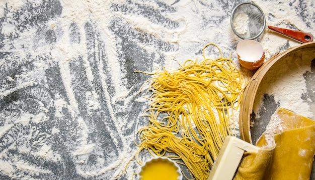 麺を調理する石のテーブルに茶漉し、卵、小麦粉を載せたパスタメーカー