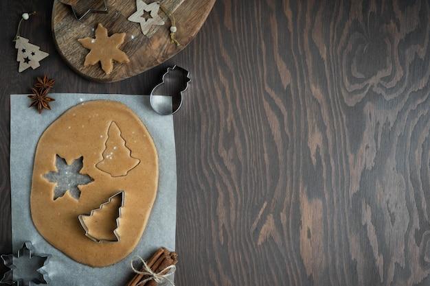 Приготовление сладких пряников из несладкого теста с корицей на темном деревянном столе