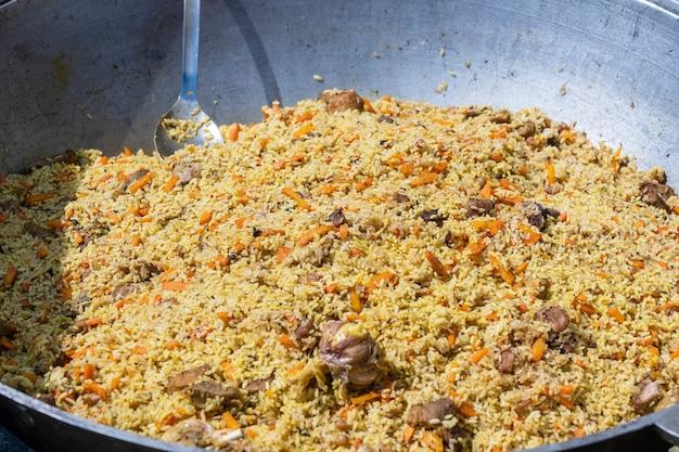 ウクライナの屋台の食品市場で大釜で伝統的なピラフを調理する、クローズアップ