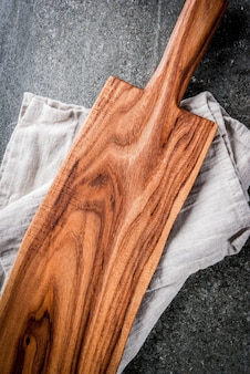 Cooking , old wooden cutting board with kitchen towel on black stone table. top view, copyspace