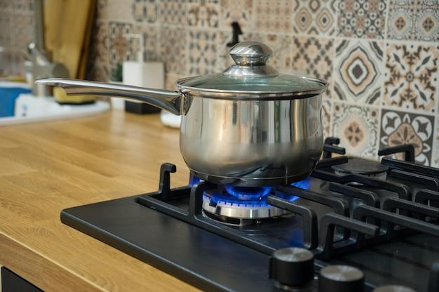 Готовим на газовой плите. горшок на газовой горелке. концепция домашней кухни.