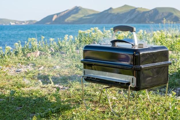 バーベキューグリルで調理。アウトドア。海のビーチと山の近く