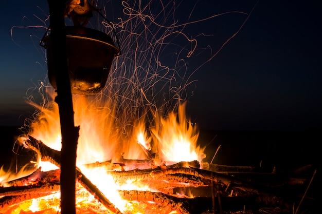 Готовим на костре для походного горшка над костром на открытом воздухе романтика дикого туризма и ...