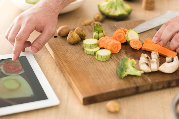 Cooking online or learning cooking concept. man preparing vegan dish while watching recipe on the internet using tablet