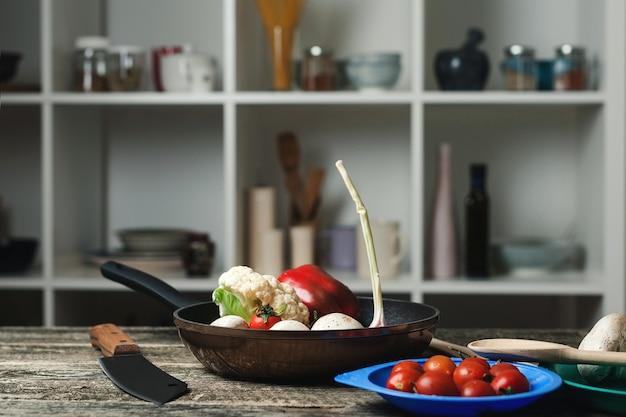 부엌 카운터에서 팬과 채식 요리 재료를 요리하십시오. 흐림 부엌 방 배경에 기구입니다. 프라이팬과 야채와 음식 요리 배경입니다.