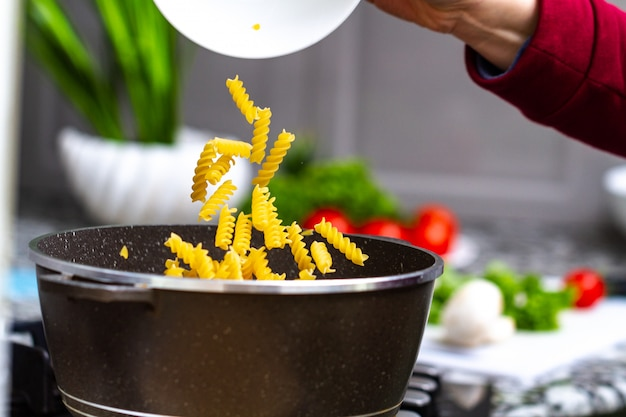 Cooking pasta at home for a lunch. pouring fusilli in a saucepan