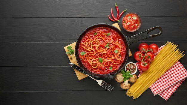Cooking pasta with tomato sauce in cast iron pan served with red chili pepper, fresh basil, cherry-tomatoes and spices over black wooden table, food cooking concept, top view, copy space