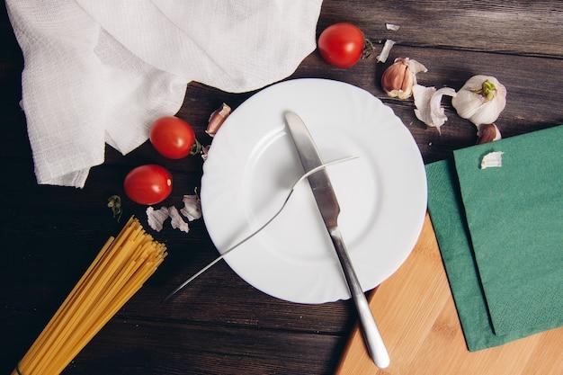 トマトキッチンテーブルでパスタを調理ホワイトプレートとフォークでナイフ