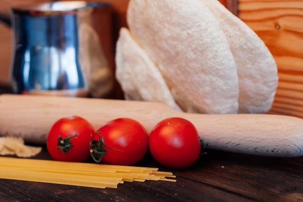 トマトキッチンテーブル木製麺棒でパスタを調理
