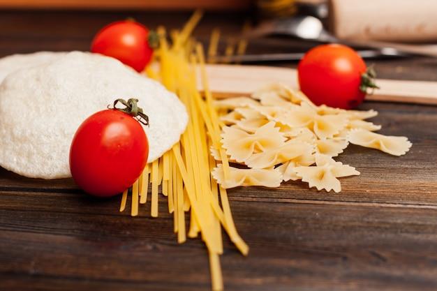 トマト、キッチンテーブルでパスタを調理