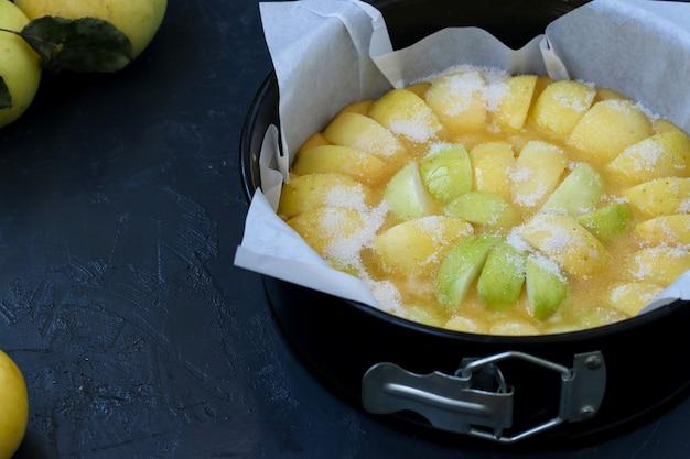 사과와 파이 요리. 반죽을 양피지로 틀에 붓고 사과를 그 위에 놓고 설탕을 뿌립니다.