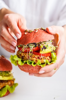 Cooking pink vegan burgers with beans cutlet, avocado and sprouts on white