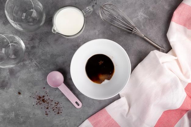 Готовим популярный корейский кофе dalgon шаг за шагом. растворимый кофе, сахар и горячая вода добавляются в миску для взбивания кофе. плоская планировка, вид сверху
