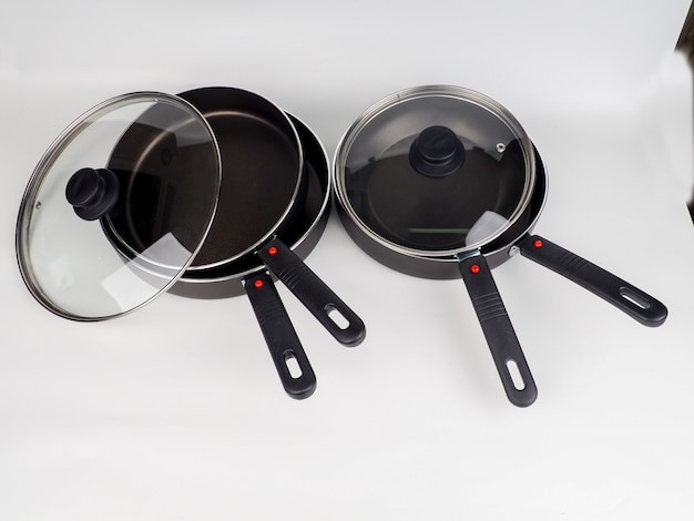 Cooking pot and frying pans on white surface