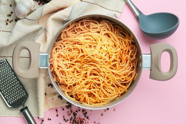 Кастрюля с макаронами и посудой на цветной поверхности