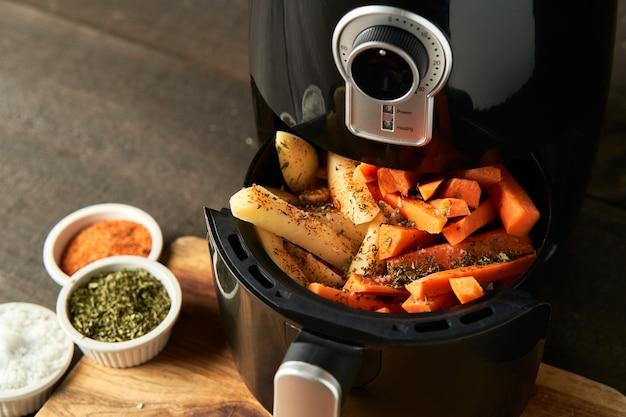 ジャガイモとにんじんスティックをエアフライヤーでスパイスで調理する