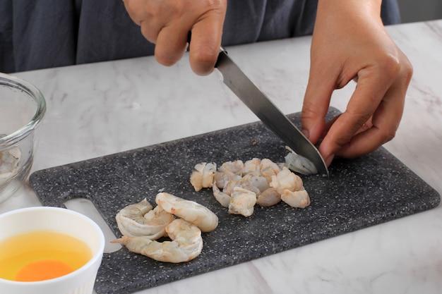 Подготовка к кулинарии: женщина-повар нарезала креветки / креветки ножом на черной разделочной доске на кухне. пошаговое приготовление пельменей / димсам с курицей и креветками