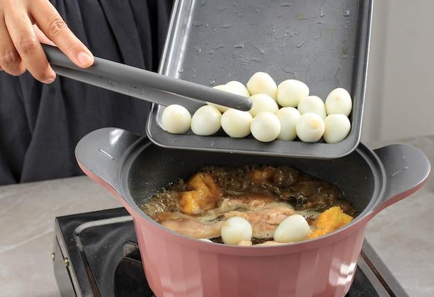 調理プロセス:ゆでたウズラの卵を追加し、オポールアヤム(インドネシアのチキンカレー)を豆腐とウズラの卵で調理し、キッチンで調理します。ゆで調理