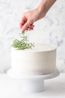 調理プロセス。菓子職人は白いクリームとローズマリーの葉でケーキを飾ります
