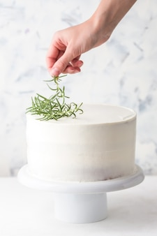 Cooking process. confectioner decorates cake with white cream and rosemary leaves