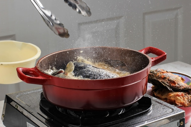 Cooking process at home oil splatter during cooking fish with red pan