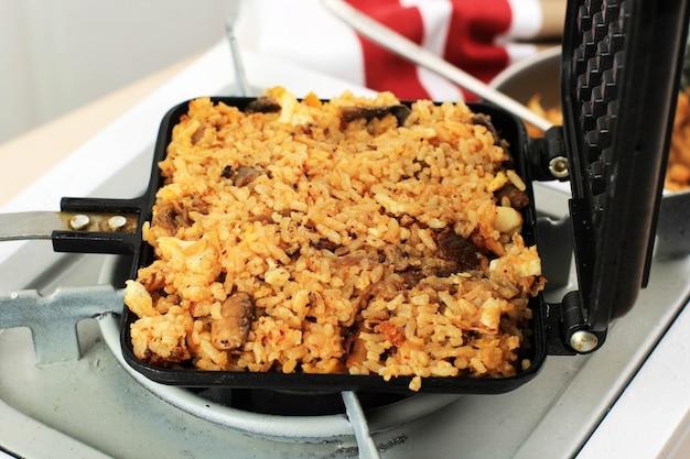 Процесс приготовления: приготовление вафель с жареным рисом кимчи (kimchi bokkeumbap) или вафлями наси горенг, модный вирусный рис, прессованный с использованием вафельницы, популярный в южной корее