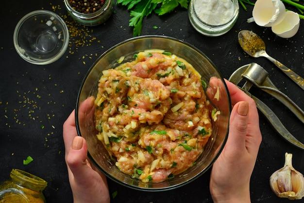 調理プロセス。ひき肉と材料、塩、コショウ、スパイス、玉ねぎ、卵、パセリ、材料をスプーンで混ぜます。女性はミートボールのためにミンチチキンを準備しています。上面図。