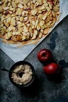 사과 소용돌이의 요리 과정. 황 설탕과 사과 두 개를 넣어 사과와 땅콩 버터를 뿌려 반죽합니다. 평면도. 플랫 레이