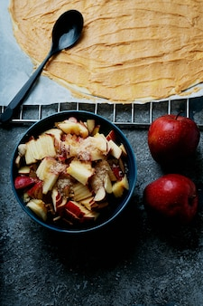 Процесс приготовления яблочных завитков. тесто с пастой из арахисового масла и нарезанными яблоками с коричневым сахаром и двумя яблоками. вид сверху. плоская планировка