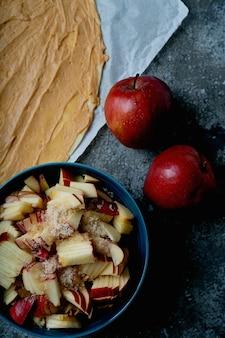 사과 소용돌이의 요리 과정. 땅콩 버터를 뿌려 반죽하고 갈색 설탕과 사과 두 개로 사과를 자릅니다. 평면도. 플랫 레이