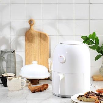 주방에서 화이트 미니 에어프라이어로 조리하는 과정. 에어프라이어로 요리하는 것은 기름을 사용하지 않거나 기름을 적게 사용하는 건강한 튀김 스타일입니다.