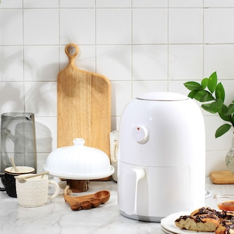 Cooking process using white mini air fryer in the kitchen. cooking with air fryer is healthy frying style with no oil or less oil