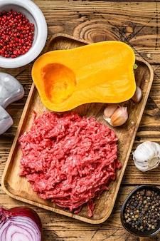 カボチャをミンチ肉、ニンニク、タマネギで調理します。木製の背景。上面図。