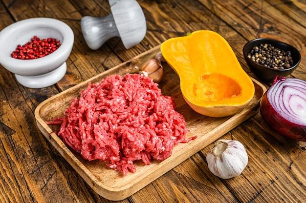 다진 고기, 마늘, 양파로 호박 요리. 나무 배경입니다. 평면도.