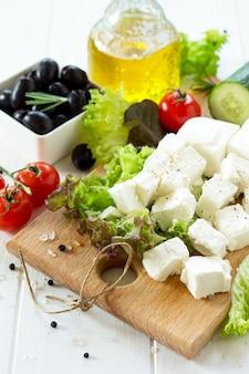 Приготовление салата из ручья со свежими овощами, сыром фета и маслинами на белом деревянном столе
