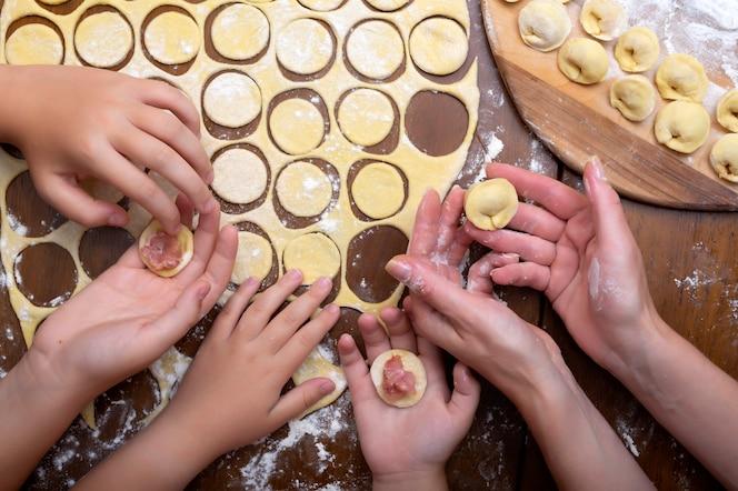 cucinare ravioli di pasta e carne con tutta la famiglia. mani di donne e bambini. gnocchi fatti in casa.