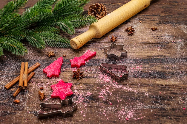 Cooking red ginger cookies. traditional christmas pastries. festive culinary background. fir tree, spices, cookie cutters, raw dough, rolling pin, wooden boards