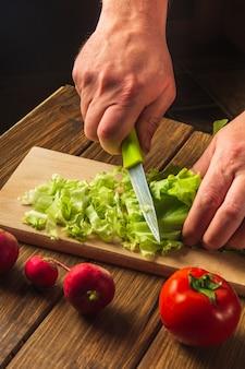 레스토랑 주방에서 요리 샐러드 요리사는 손으로 근접 촬영 컷 샐러드 채소입니다