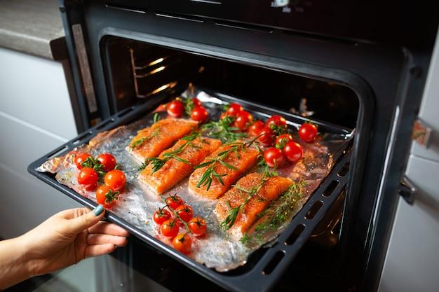 오븐에서 연어 요리하기. 주부는 저녁 식사를 준비하고 있습니다. 요리사는 빨간 물고기를 요리입니다. 오븐에서 생선 요리.