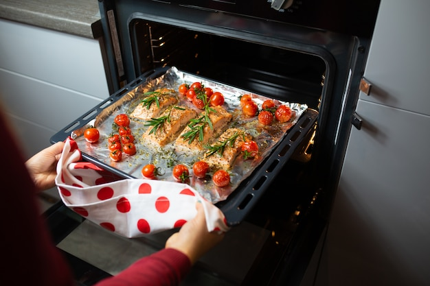 Cooking salmon in the oven. housewife is preparing dinner. chef is cooking red fish. cooking fish in the oven.