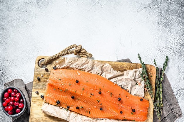 ハーブとスパイスと木製のまな板で塩漬けのサケの切り身を調理します。灰色の背景