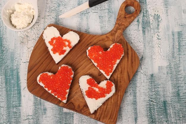 Готовим бутерброды с красной икрой и сливочным сыром в форме сердца на день святого валентина, вид сверху