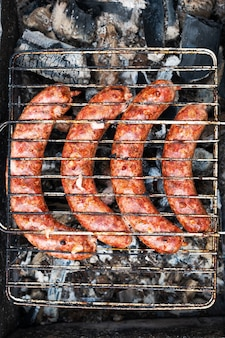 Cooking sausages on the grill in the barbecue outdoors on a picnic