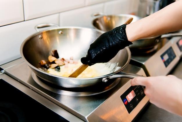カフェの金属鍋でスクランブルエッグを調理する、選択的な焦点