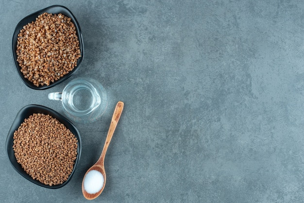 Configurazione di cottura di due ciotole di grano saraceno, una piccola brocca d'acqua e un cucchiaio di sale su fondo marmo. foto di alta qualità