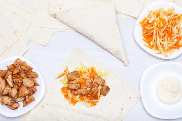 Приготовление шаурмы обернуть с лаваш, курица, соус, морковь, капуста на деревянный стол. концепция здорового быстрого питания.