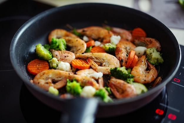 Готовим креветки с овощами на сковороде. домашняя кулинария или концепция здорового приготовления