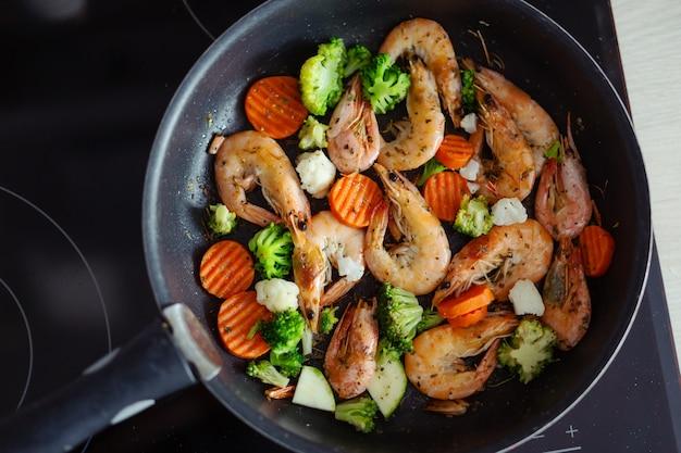 鍋に野菜を添えてエビを調理します。家庭料理または健康的な料理の概念